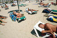 "Spain. Mallorca in the Balearic islands. Palma. Tourists take a rest, sunbathe and sleep on plastic chairs in the sandy beach of "" Playa de Palma"". © 1999 Didier Ruef"
