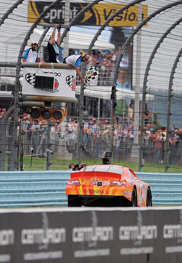 Aug. 8, 2009; Watkins Glen, NY, USA; NASCAR Nationwide Series driver Marcos Ambrose takes the checkered flag to win the Zippo 200 at Watkins Glen International. Mandatory Credit: Mark J. Rebilas-