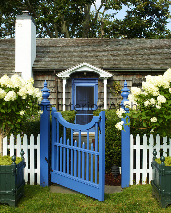 The exterior of the cottage is faced in lapped clapboard and the property has the archetypal white picket fence at the front. The front door and gate are painted blue and flowering shrubs stand in square planters either side of the gate.