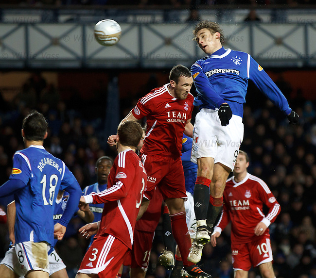 Nikica Jelavic powers a header past defender Rory McArdle