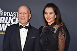 HOLLYWOOD, CA - JULY 14: Bruce Willis (L) and Emma Heming arrive at the Comedy Central Roast Of Bruce Willis at the Hollywood Palladium on July 14, 2018 in Los Angeles, California.