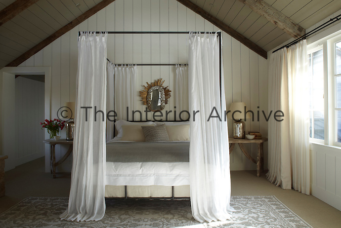 The spacious wood-lined double-height master bedroom is located in the adjacent limestone house