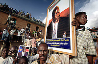 A supporter carries a portrait of John Garang de Mabior, leader of the SPLA (Sudan People's Liberation Army), during celebrations to mark Garang's swearing-in as Vice President. The ceremony followed a peace agreement between the North and South which ended years of civil war. Three weeks later Garang died in a helicopter crash.