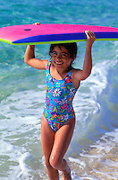 Little girl smiling and playing with boogieboard on the beach at the north shore