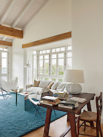 The open-plan sitting room has exposed ceiling beams and a wood floor. The light decoration creates a fresh and airy feel whilst the rough wooden writing table and chair gives a rustic ambiance. The blue rug lends a bold spot of colour in the otherwise neutral room.