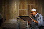 A Palestinian man reads Quran at Al-Omari mosque during the holy month of Ramadan in Gaza city on August 30,2010. Photo by Mustafa Hassona