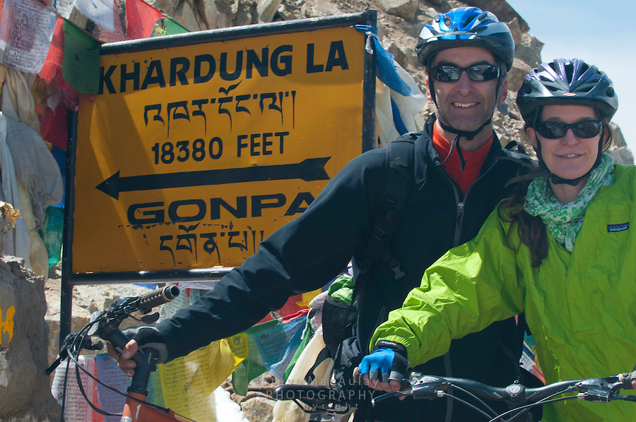 Portrait of two mountain bikers at Khardung La at 18,380ft. the summit of the highest motorable road in the world.  Himalayan Mountains, Ladakh, India.