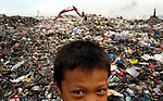 A child working in the municipal dump in Manila, the capital of the Philippines. Children and their parents work day and night in the dump, scavenging for items of value, including plastic, glass and metal, that can be recycled..