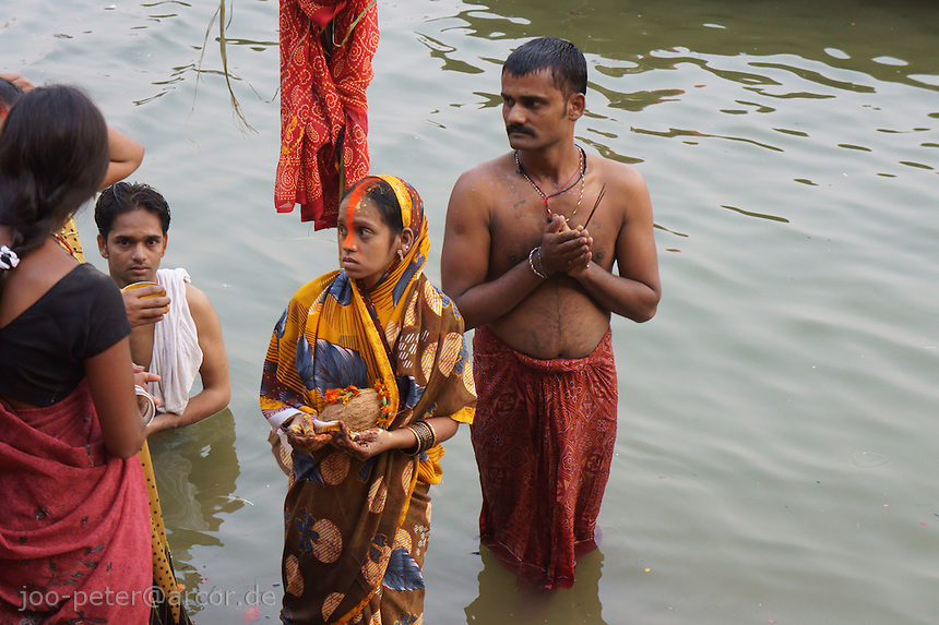 family praying in river Ganges during chat mata, holy day of  mothers praying  for relief, in holy city Varanasi, India  31. Oktober 2011 (chat mata is also called Dala chhath). in this ceremony women gather at the river and pray for sons and good luck of her family (a woman without a son is belived to end up in hell, also a widow is believed to be cursed and can be expelled by the family).God of the sun, Surya is asked for help in Dala chhath. Surya is one of the most acient gods in India, already known in Vedic times, where Shiva and Brahma were still unknown.