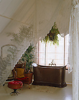 A piece of antique lace separates bedroom and bathroom in this white-painted attic