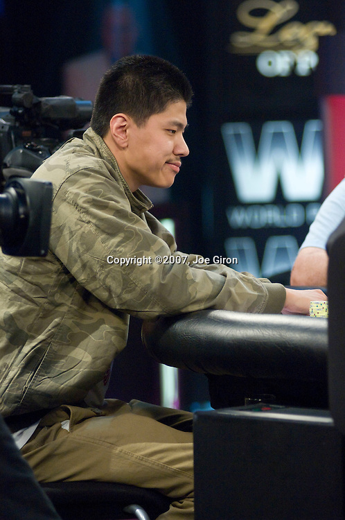 Shi Jia Liu reacts to seeing he is behind after showing his cards.