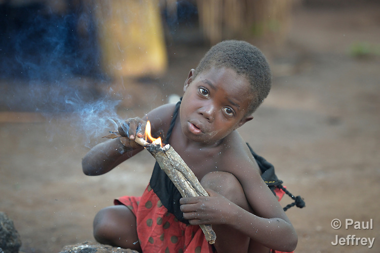 Three-year old Hiyatzi Simon blows on an ember as she starts a cooking fire in a camp for more than 5,000 displaced people in Riimenze, in South Sudan's Gbudwe State, what was formerly Western Equatoria. Families here were displaced at the beginning of 2017, as fighting between government soldiers and rebels escalated.<br />