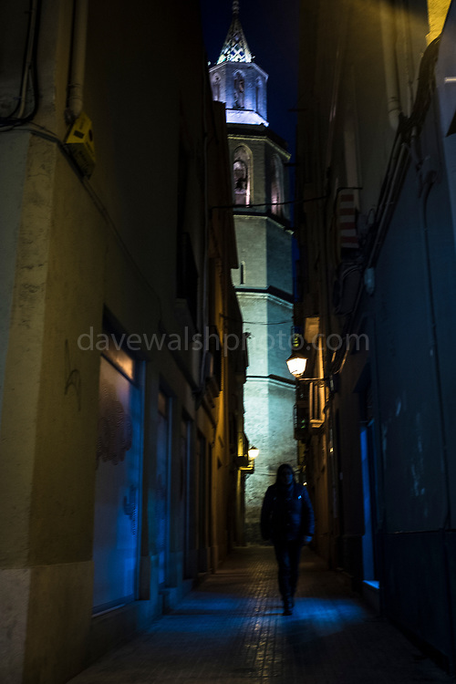 A person walks through an alleyway near Basílica de Santa Maria, Vilafranca del Penedes, Catalonia.
