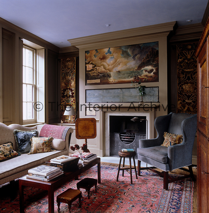 The drawing room overmantel is decorated with a hand-painted mural by Ian Harper and either side of the chimney breast hang lengths of a 17th century Venetian tapestry