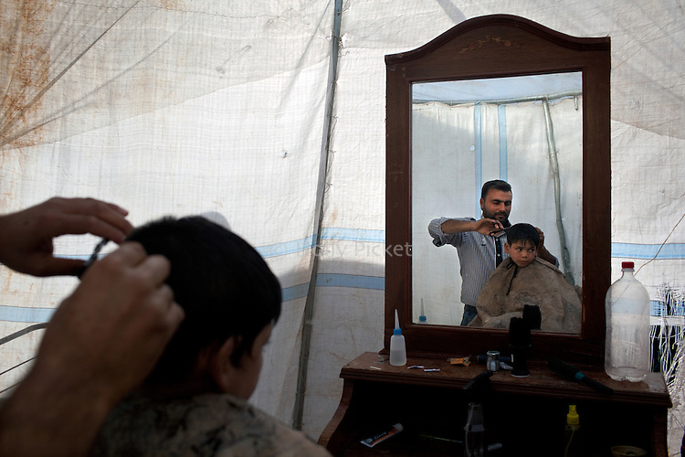 Riyadh Zeyduh cuts 6-year-old Romy Bakur's hair in a tent he uses as a barbershop at Azaz Camp, just inside the Syrian border with Turkey, Feb. 21, 2013. According to administrators, this camp holds roughly 9,000 to 10,000 internally displaced persons (IDP's). The UN Refugee Agency has reported a sharp increase in refugees fleeing Syria for neighboring countries in the first months of 2013.