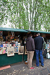 Two men shop for vintage books and magazines at a sidewalk stall, Paris, France