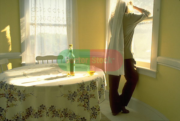 depressed man looking out window with bottle of liquor on table