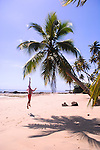 Man jumping to touch a beachside coconut palm on the island of Boipeba, just south of Salvador, Brazil.