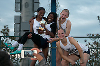 The Lee's Summit West sprint medley relay team of K. Atkins, E. Sermons, J. Shawver, and Nicole Kallenberger pose with their trophy after their victory in the event in 4:12.68 at the 2015 Kansas Relays.
