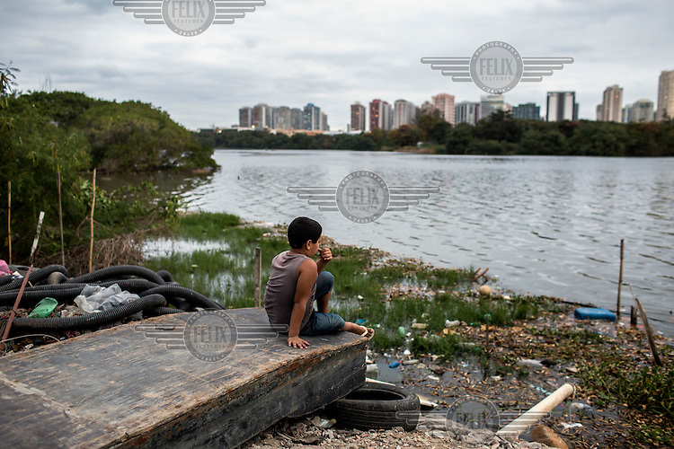Pedro Feritas, eight, sits on the shore of Lagoa da Tijuca, in the working class community of Rio das Pedras across the lake from estates of  high-rise condominium complexes.