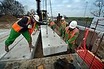 """VEENENDAAL - Tijdens de bouw van een betonnen viaduct als onderdeel van de A12 snelwegverdubbeling werken (bijna) alle medewerkers van BAM Civiel ondanks het bewolkte weer, met een mooie zonnebril op. Ze zijn sinds deze maand verplicht de gele veiligheidsbril te dragen om oogletsel tijdens het werk, te voorkomingen. Hoewel de bril lichtgewicht is, en makkelijk past, is het even wennen, want door de gele bril ziet de wereld er heel anders uit, blijkt als het tijd is om te pauzeren. """"Je ziet de wereld de hele dag met een kleurzweem,"""" aldus één van de mannen. """"En ik weet niet of ik daar blij mee moet zijn."""" COPYRIGHT TON BORSBOOM"""