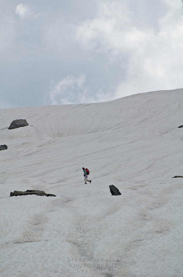 Solitary trekker with backpack crossing glacier segment, Western Himalayan Mountains, Kashmir, India..