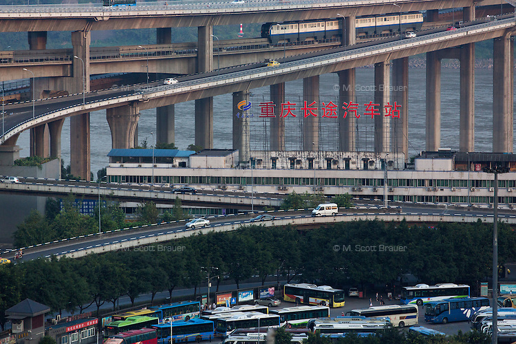 Cars and buses travel along elevated roads in the Yuzhong District of central Chongqing, China.
