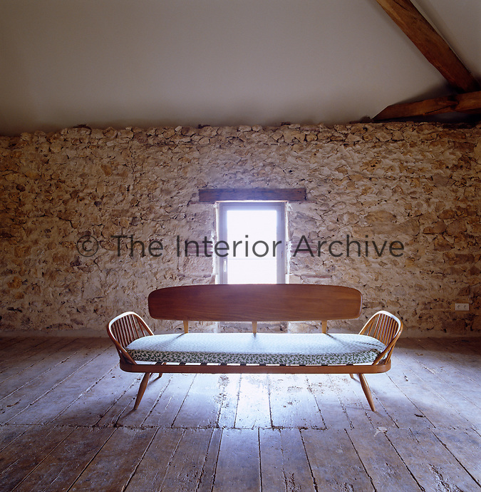 An Ercol sofa stands in the middle of the wooden floor of the former granary