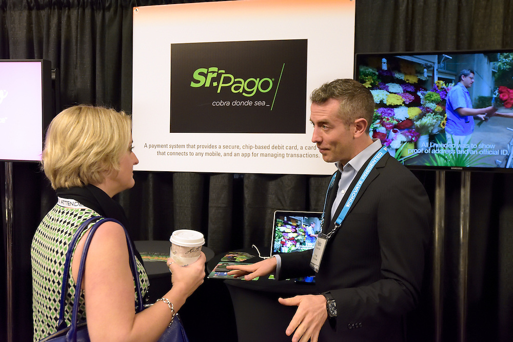 Candid photo of vendor and attendee at a trade show.