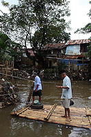 Local men stand on a river raft in a slum community in central Jakarta.<br /> <br /> To license this image, please contact the National Geographic Creative Collection:<br /> <br /> Image ID:  1588044<br />  <br /> Email: natgeocreative@ngs.org<br /> <br /> Telephone: 202 857 7537 / Toll Free 800 434 2244<br /> <br /> National Geographic Creative<br /> 1145 17th St NW, Washington DC 20036