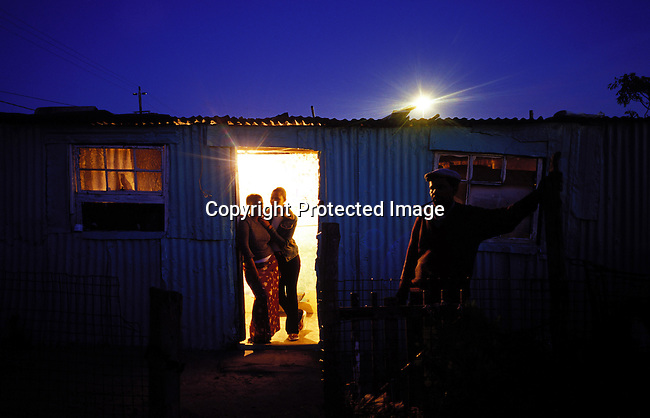 ditown00268.Digital. Townships. Eric France, age 57, front, smoking a pipe outside his shack as his daughter Nslusineliso France, age 22, and her friend Lindiwe Mqhle, age 20, stand in the doorway, in the evening on November 3, 2003 in Site C in Khayelitsha, South Africa. Townships. Poverty, lights burning brightly in shack. .©Per-Anders Pettersson/iAfrika Photos