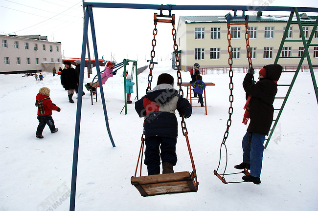 Children played in a new playground outside a newly built school in the village of Amguema in the Artic Circle in the north of Chukotka.  Amguema, Chukotka Autonomous Okrug, Russia, April 4, 2007.