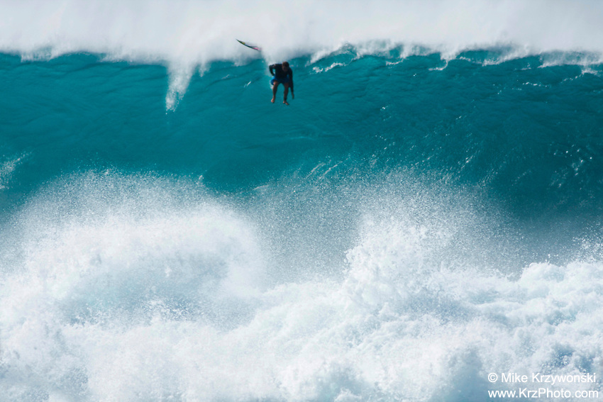 Surfing free falling from top of big wave at Pipeline on the North Shore of Oahu