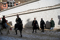 Men on horses prepare to lead Tibetan Buddhist Monks of the Gelugpa Order (Yellow Hat Sect) as they accompany a thangka (painting of Buddha) through the streets of Xiahe, Gansu Province, China, during the Monlam Festival at the Labrang Monastery.  Monks work on the painting for the year preceding the festival and then display it on a nearby hillside for about an hour.