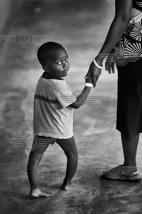 A young boy walks with his mother in the CCBRT (Comprehensive Community Based Rehabilitation in Tanzania) Disability Hospital.