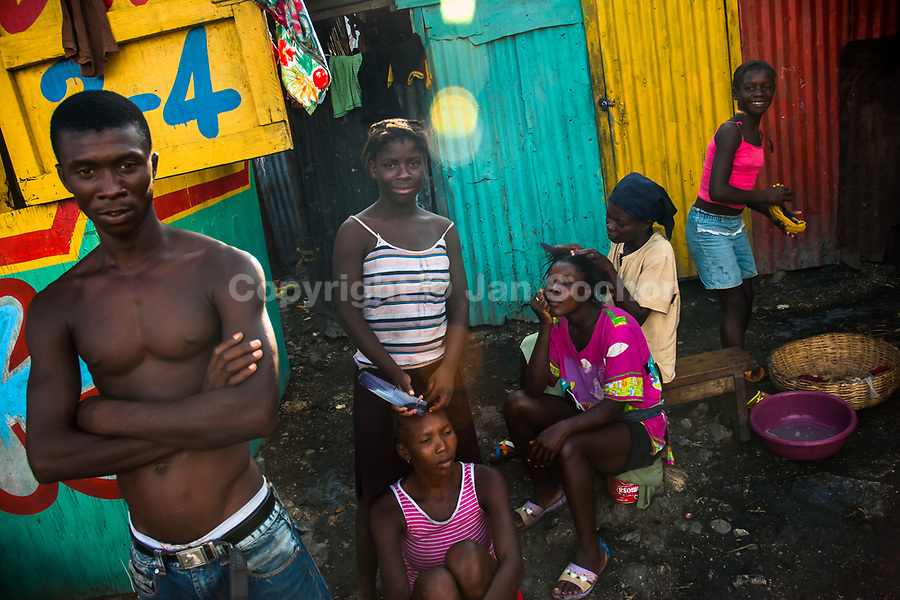 Young Haitian girls and women style their hair on the street inside a shanty town in Port-au-Prince, Haiti, 22 July 2008.