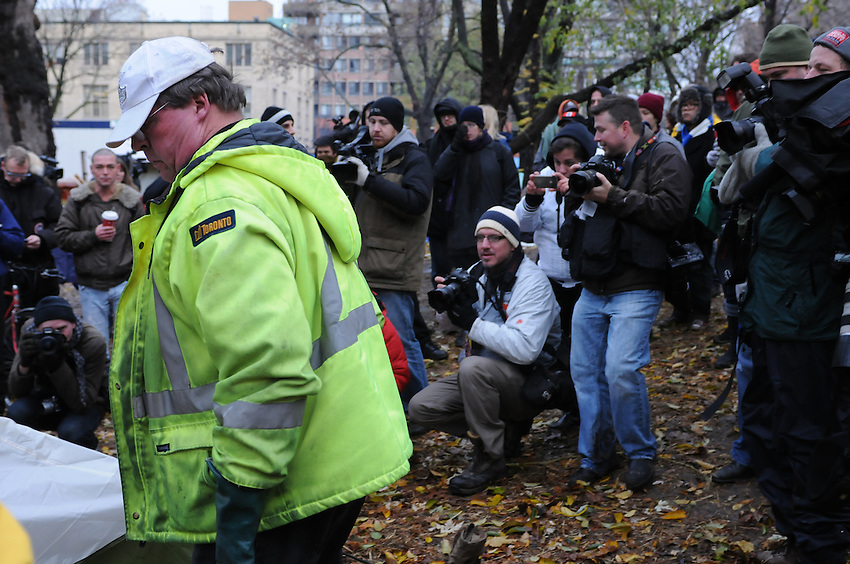 November 23, 2011, Toronto Police and city workers arrived in significant numbers early this morning, beginning the process of evicting the Occupy Toronto tent camp from St. James Park.  Here throngs of media and protest supporters focus upon one city worker beginning the camp tear down.