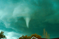 A funnel could in the sky decends over the rooftop of a house.