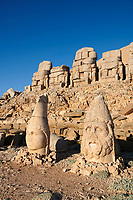 Statue heads, from right, Herekles & Apollo with headless seated statues in front of the stone pyramid 62 BC Royal Tomb of King Antiochus I Theos of Commagene, east Terrace, Mount Nemrut or Nemrud Dagi summit, near Adıyaman, Turkey
