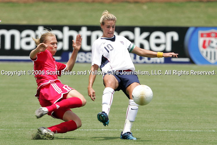 30 July 2006: U.S. midfielder Aly Wagner (10) tries to play the ball away from the tackle of Canada's Brittany Timko (left). Wagner earned her 100th cap with her start.The United States Women's National Team defeated Canada 2-0 at SAS Stadium in Cary, North Carolina, in an International Friendly match.