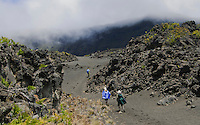 Three male hikers with backpacks walking throught the lava fields in the crater of HALEAKALA NATIONAL PARK on Maui in Hawii USA