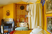 In this bedroom a faded red and white wall hanging is arranged against the buttercup-yellow walls