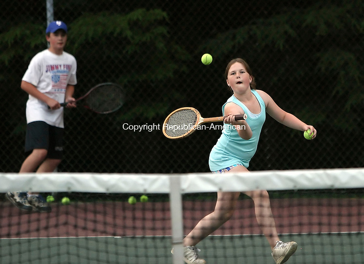 SOUTHBURY, CT 7/01/07- 070107BZ02- Julia Low-Chapel, 9, returns a shot while playing tennis with her brother Sam Low-Chapel, 12, in background, and mother Lisa Low at Community Park in Southbury Sunday.  <br /> Jamison C. Bazinet Republican-American