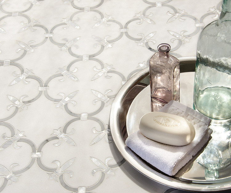 Fleur de Lys, a waterjet stone mosaic, shown in polished Thassos, polished Carrara, and Shell, is part of the Jardins Français collection by Caroline Beaupere for New Ravenna.