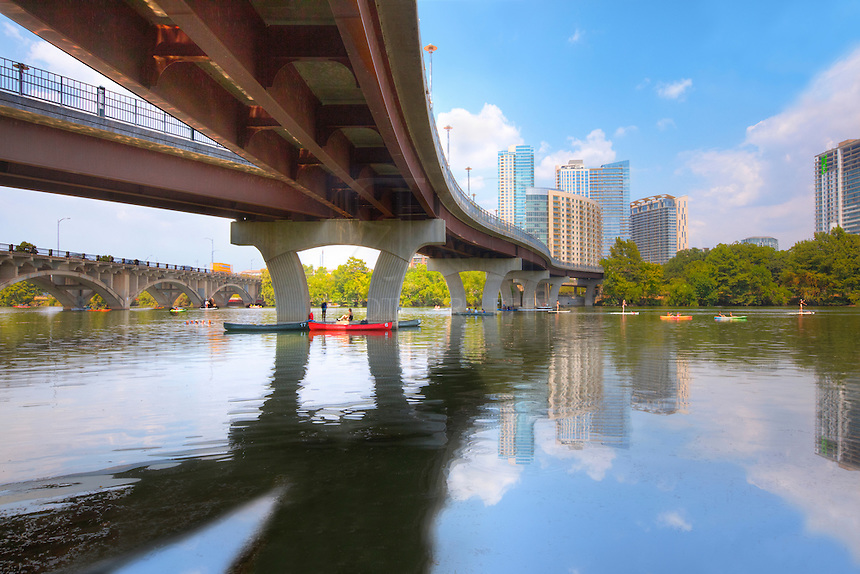 The Colorado River flows through Lady Bird Lake on a hot August afternoon. In the distance, the Austin skyline rises into the warm air while paddle-boarders and kayakers enjoy the cool water.