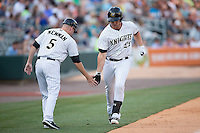 Matt Davidson (22) of the Charlotte Knights slaps hands with third base coach Ryan Newman (5) after hitting a home run against the Indianapolis Indians at BB&T BallPark on June 20, 2015 in Charlotte, North Carolina.  The Knights defeated the Indians 6-5 in 12 innings.  (Brian Westerholt/Four Seam Images)