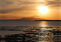 The sun sets behind Mt. Susitna, also known as Sleeping Lady, as seen from Anchorage, Alaska.