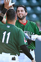 Designated hitter C.J. Chatham (10) of the Greenville Drive high-fives Victor Acosta after scoring the first run in a game against the Charleston RiverDogs on Sunday, April 29, 2018, at Fluor Field at the West End in Greenville, South Carolina. Greenville went on to win 2-0. (Tom Priddy/Four Seam Images)