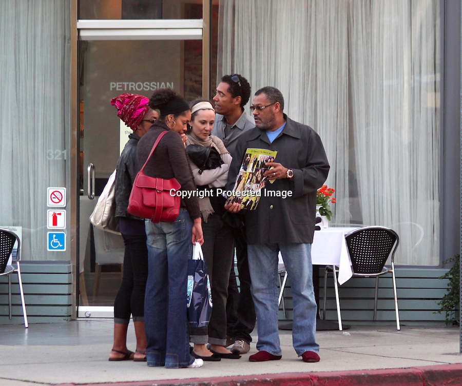......January 2nd 2012  Exclusive ..Beverly Hills California..Laurence Fishburne showing his family a picture of him in a tabloid magazine called Beverly Hill Street. Then Laurence walked his wife to  their Maserati & opening the car door for her. ..AbilityFilms@yahoo.com.805-427-3519.www.AbilityFilms.com.....