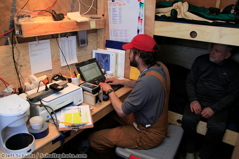 "Volunteer communications volunteers Mike Holland and Grant Jacobson work via SAT phone inside their ""comms"" shack at the ghost-town checkpoint of Iditarod during the 2011 Iditarod race.."